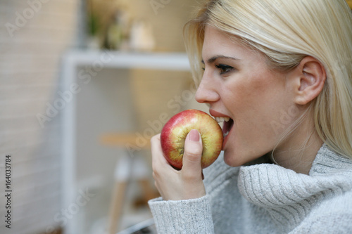 Woman eating a red apple. Smiling woman eating a red apple at home.