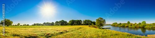 Landschaft im Sommer mit Bäumen, Wiesen, Fluss und Sonne