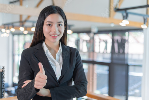 portrait happy business woman thumbs up in the office