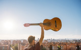 Boy lifts guitar in a park of madrid spain