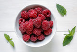 raspberries in a bowl on white background - 164056356