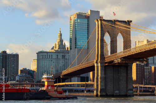 The Brooklyn Bridge stands against blue sky downtown Manhattan skyscrapers Poster