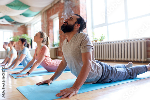 group of people doing yoga cobra pose at studio - 164082732