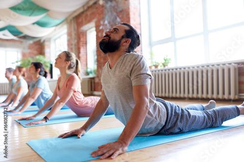 group of people doing yoga cobra pose at studio - 164082732