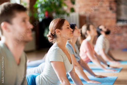 Leinwanddruck Bild group of people doing yoga cobra pose at studio