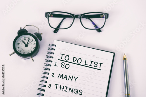 To do list written on a notepad with eyeglasses, pen and alarm clock, film effect Poster