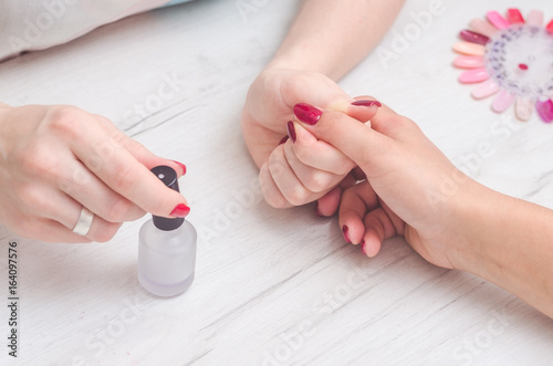 The girl of the manicurist paints the nails