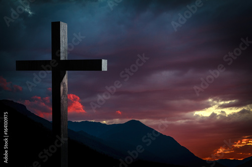 Jesus Christ cross on a background with dramatic sky and colorful, red, orange, purple sunset on blue mountains Poster