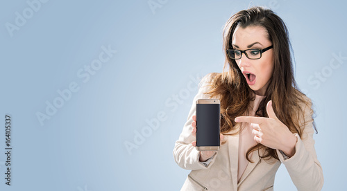 Amazed brunette lady poiting a cell phone