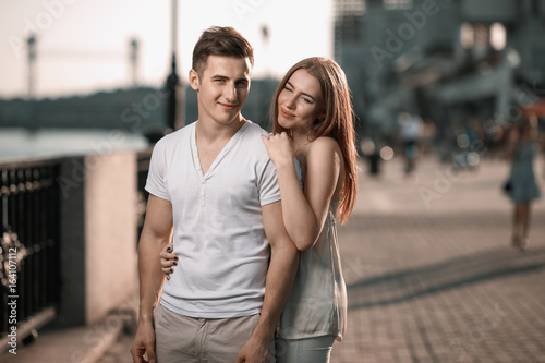 Portrait of young couple in love, enjoying the sunset in city
