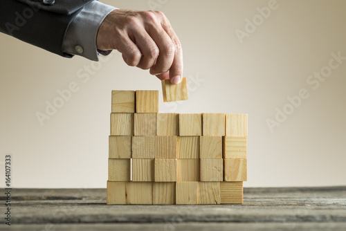 Businessman building a structure with wooden cubes on table surface - 164107333