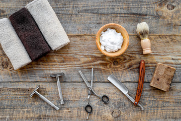 Barbershop. Men's shaving and haircut. Brush, razor, foam, sciccors on wooden table background top view