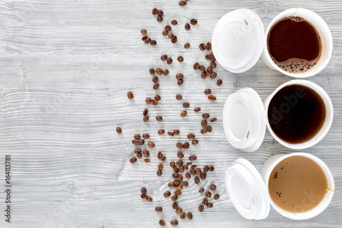 Papiers peints Cafe Coffee to go. Coffee cups with cover and coffee beans on wooden table backound top view copyspace