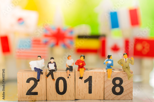 Poster Miniature people : sitting on 2018 wooden number using as business concept