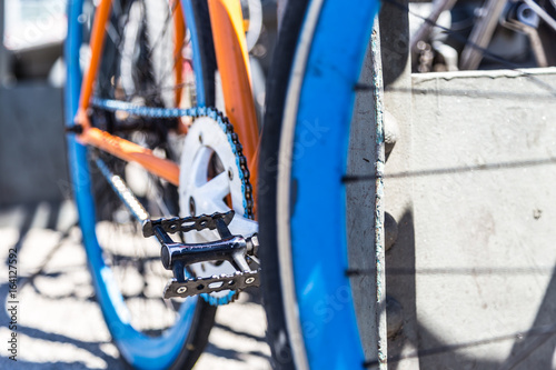 Poster Fiets Closeup of blue, orange and white hipster urban bicycle. Focus on chainring.