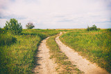 Retro toned photo of country road - 164131181