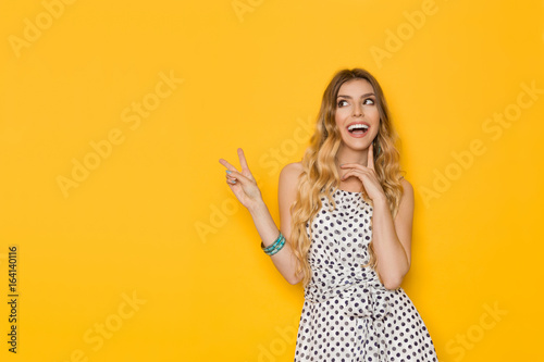 Laughing Young Woman In Dotted Dress Is Showing Peace Sign - 164140116