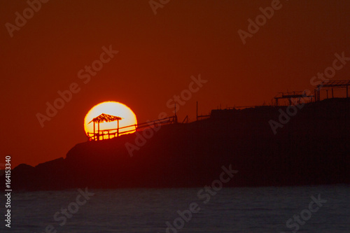 Fotobehang Rood paars GAZEBO ON THE BEACH WITH SUNSET