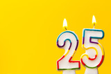 Number 25 birthday celebration candle against a bright yellow background - 164169999