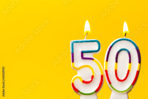 Number 50 birthday celebration candle against a bright yellow background
