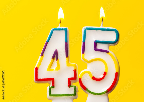 Number 45 birthday celebration candle against a bright yellow background плакат