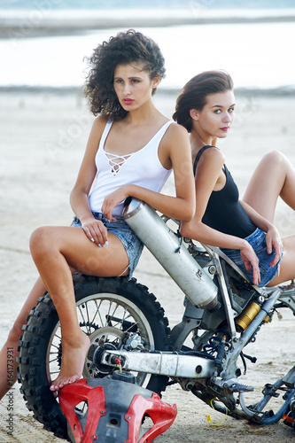 Deurstickers Beautiful sexy girl pose in front of a disassembled motorcycle