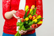 Woman holding yellow and orange bouquet of tulips - 164195781