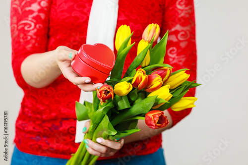 Woman holding yellow and orange bouquet of tulips Poster