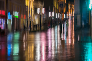 Abstract bright blurred background with unidentified people city street in rainy night. Vivid illumination, reflection in wet pavement from shop windows, street lamps. Concept active lifestyle
