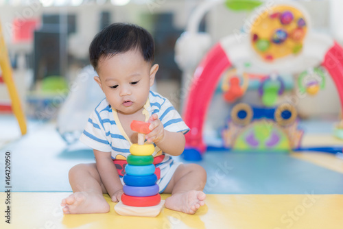 Adorable Asian baby boy 9 months sitting and playing with color developmental toys in kids room at home..