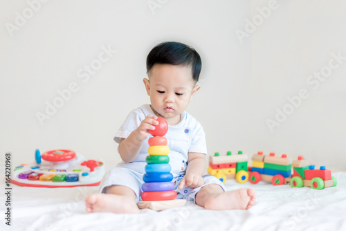 Adorable Asian baby boy 9 months sitting on bed and playing with color developmental toys at home..