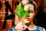A girl with a cannabis leaf near her face