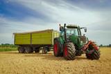 Getreideernte - Trecker mit Anhänger auf einem Stoppelfeld - 164250171