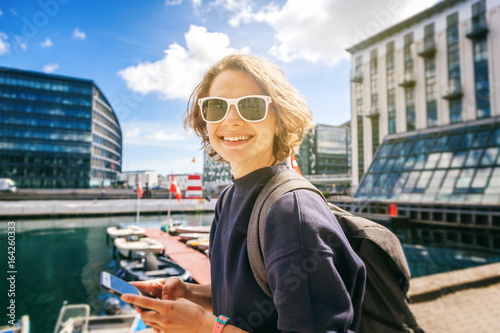 Happy young stylish woman with mobile phone in hands on city background