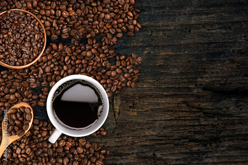Coffee background, top view with copy space. White cup of coffee and, ground coffee, coffee beans on dark wooden background
