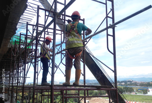 Construction workers wearing safety harness and adequate