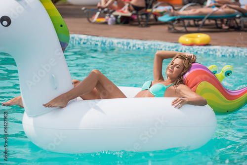 Beautiful young blonde in a swimsuit, swims and relaxing in the pool on a white inflatable unicorn