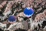 Aerial view over balloons flying over rocky landscape in Cappadocia, Turkey. - 164282793