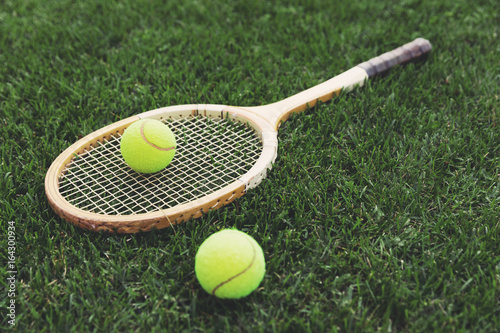 vintage wooden tennis racket on grass with balls