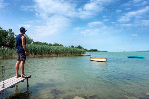 Adult man looks at Balaton Lake in the summer Poster