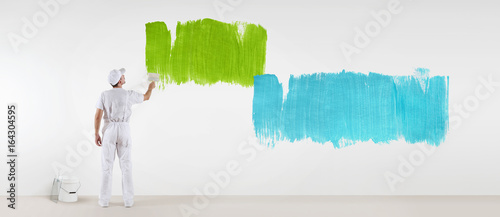 painter man with paint brush painting colors samples, isolated on blank white wall background, web banner