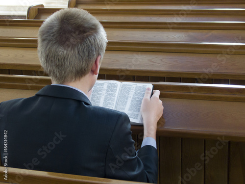 Poster Man reads the Holy Scripture in the Church