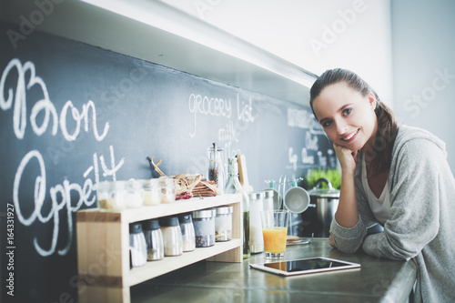Plakát Young woman with orange juice and tablet in kitchen.