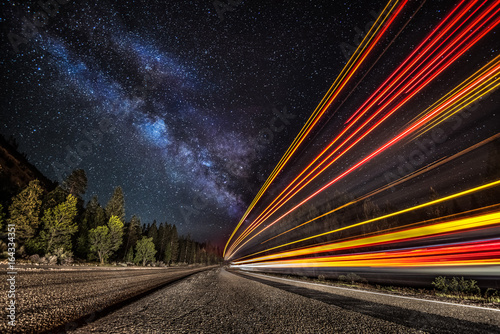 Foto op Canvas Nacht snelweg Light streaks on the highway under the Milky Way