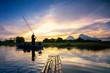 The fisherman in silhouette paddling the boat and the bamboo raft under golden aurora sunrise at the Tasoh lake, Perlis, Malaysia