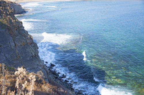 Mighty rock, collapses in a blue sea, with sun glare, majestic rocks © juliza09