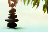 Balance concept between of Life and work present by Hand setting a natural zen rock stone stack, Surrounded with Leaf and Ripple, Side view - 164344190