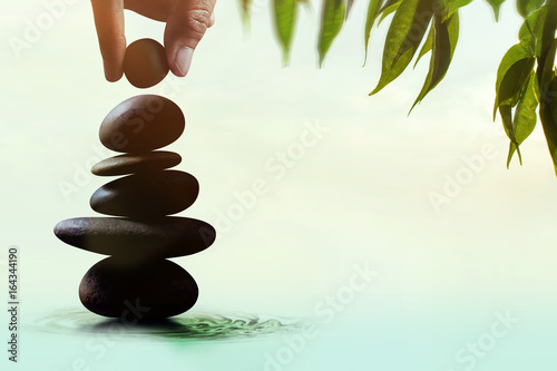 In de dag Spa Balance concept between of Life and work present by Hand setting a natural zen rock stone stack, Surrounded with Leaf and Ripple, Side view