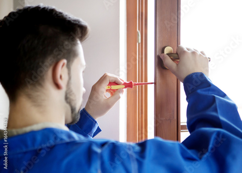 Plakat Young handyman repair window with screwdriver