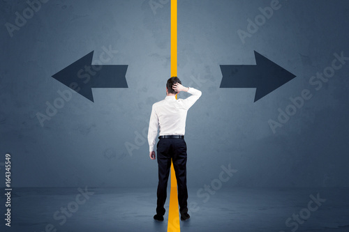 Business person choosing between two options separated by a yellow border arrow - 164345549